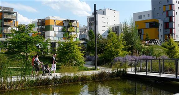 Photo : bâtiments d'habitation relativement élevés, aux formes un peu différentes et originales, dont des couleurs un peu différentes, avec plusieurs arbres et un cour d'eau.</body></html>